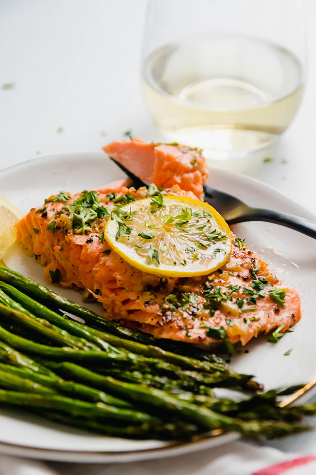 Slice of baked steelhead topped with a lemon slice on a white plate next to roasted asparagus.