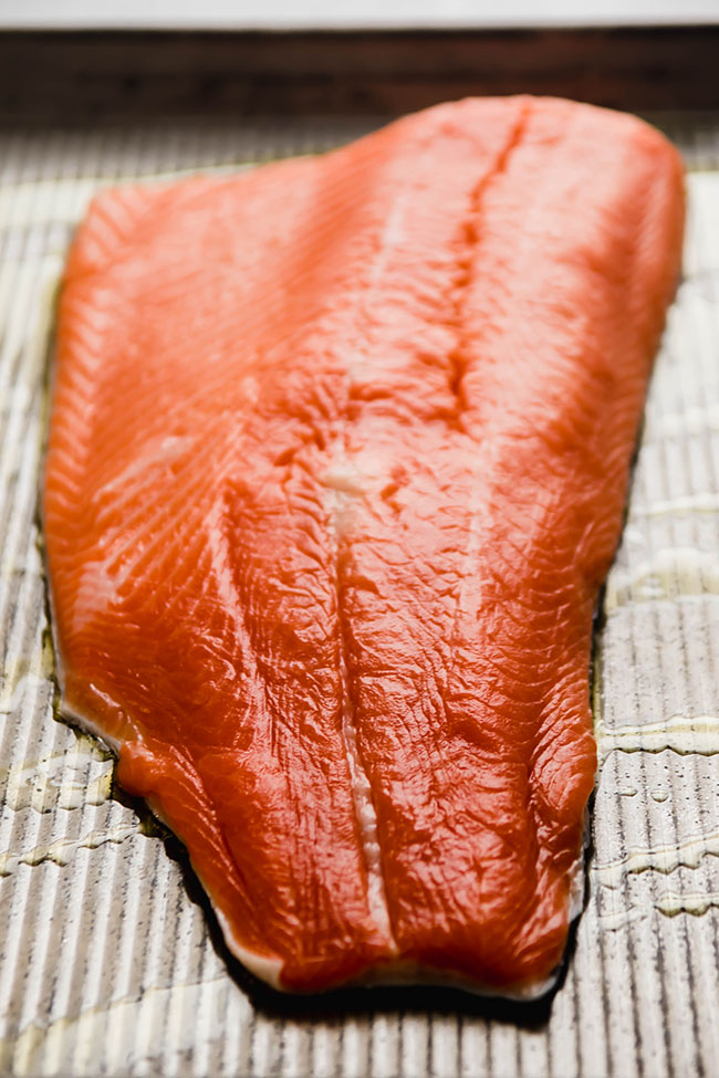 Steelhead fillet on a metal baking sheet drizzled with olive oil.