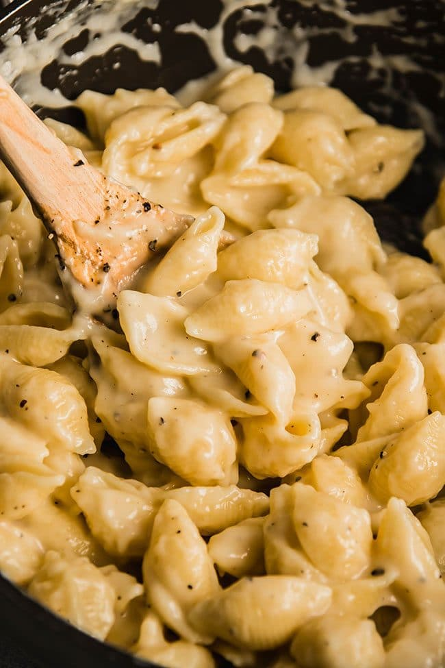 Wooden spoon stirring macaroni and cheese made with shell pasta.