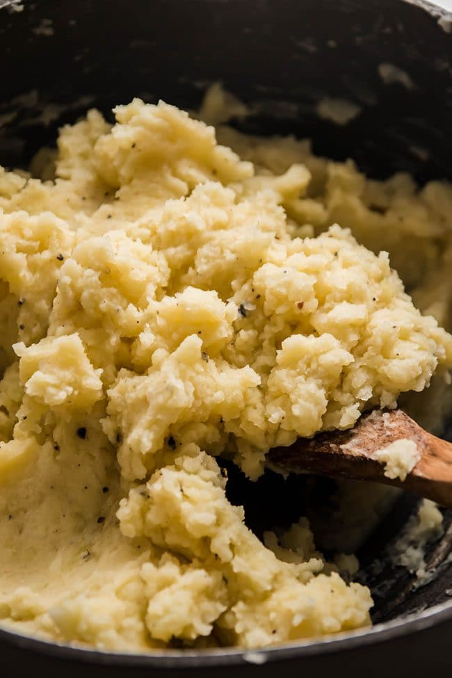 Wooden spoon stirring cauliflower mashed potatoes in a large pot.