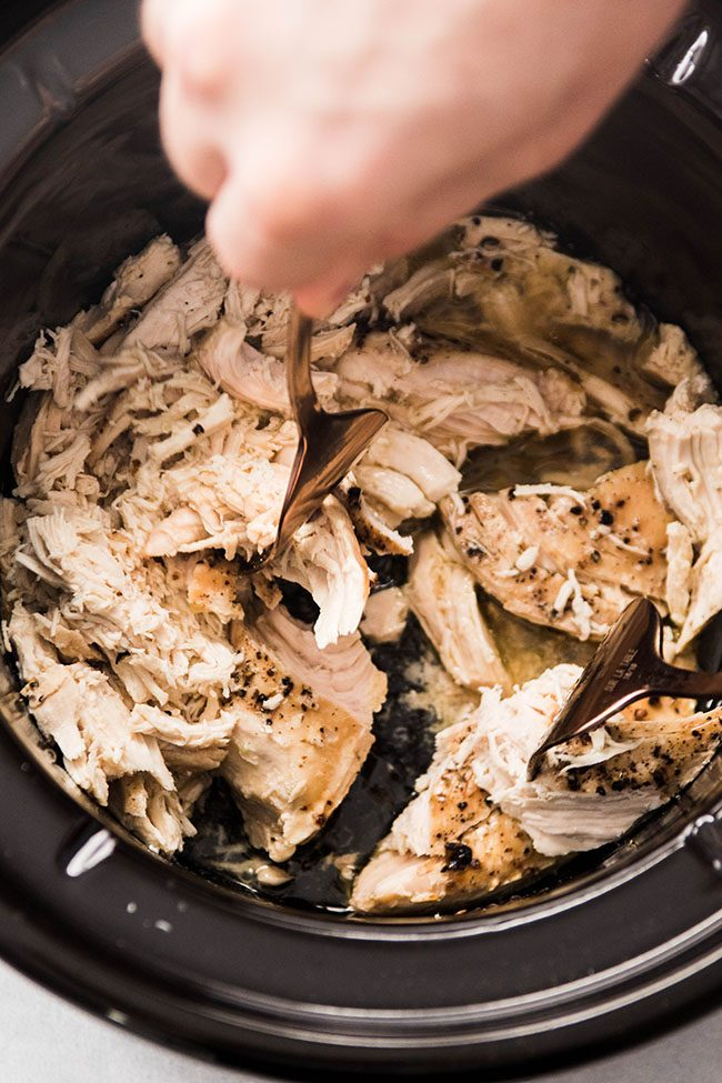 Man's hands using forks to shred cooked chicken in a slow cooker