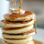 White dish pouring maple syrup over a stack of pancakes.