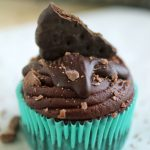 Chocolate cupcake in a green wrapper, topped with shaved chocolate and a cookie.