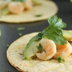Shrimp, avocado, and fresh cilantro on a corn tortilla.