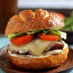 Chicken sandwich on a wooden plate.