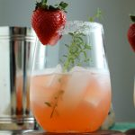 Wine glass filled with strawberry margarita and a sprig of fresh thyme.