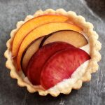 Small tart shell filled with sliced stone fruit.