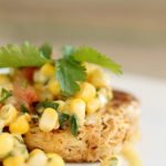 Crabcake topped with corn and cilantro.