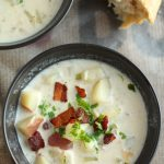 Clam chowder topped with crispy bacon in a black bowl.