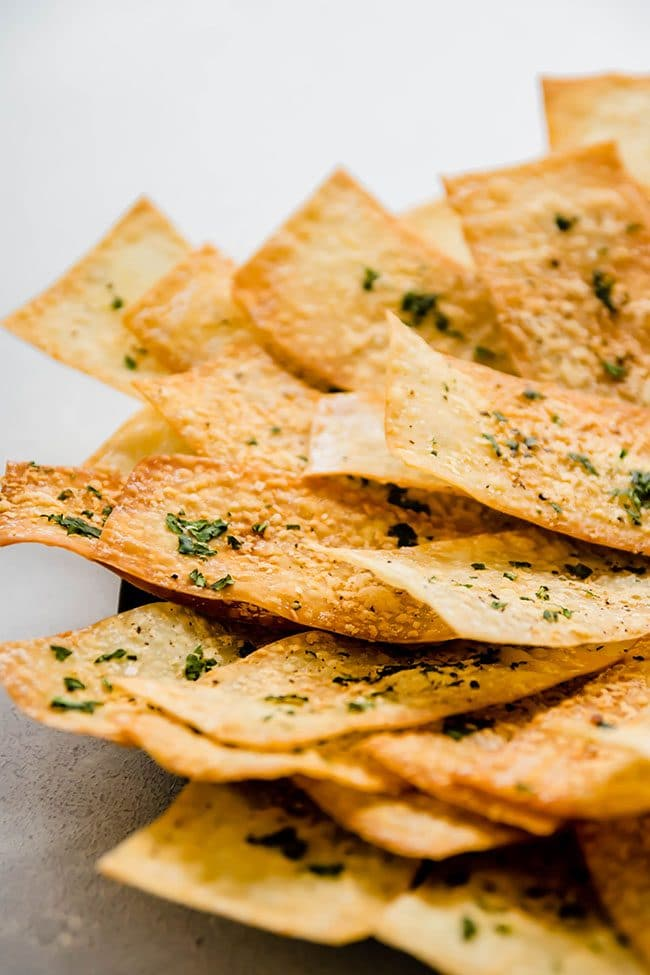 Thin parmesan wonton crackers in a pile on a black plate.