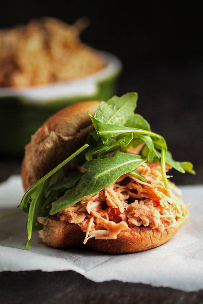 sandwich roll with shredded chicken and arugula on a dark background