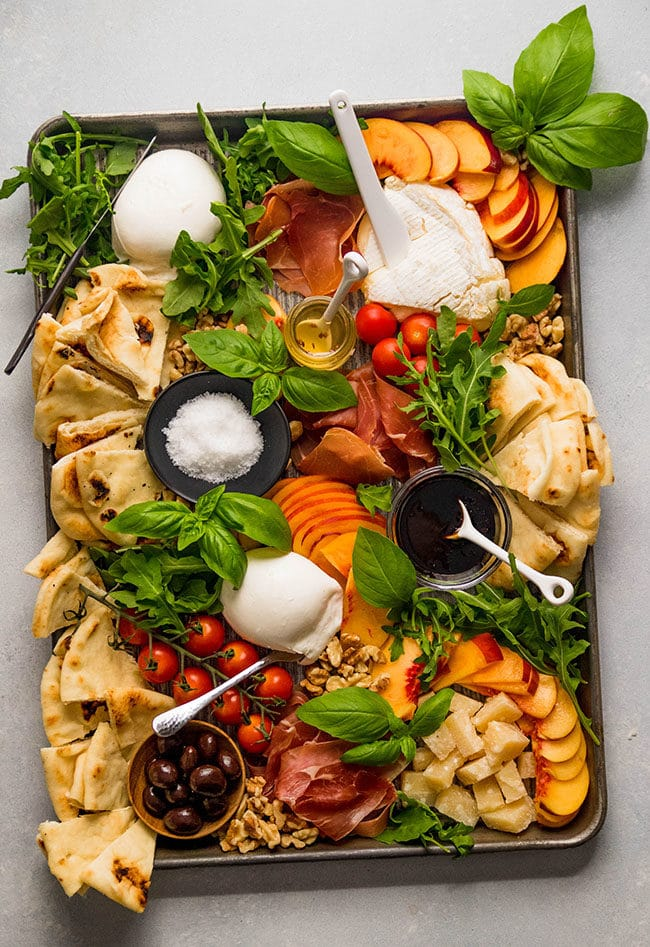 Overhead photo of various cheeses on a sheet pan with peaches, tomatoes, and basil.