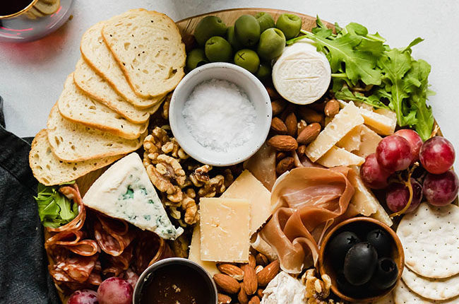 Overhead photo of an assortment of cheeses on a wooden cutting board