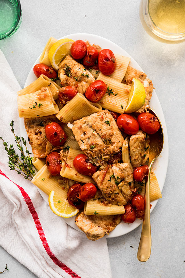 overhead photo of rigatoni and barramundi fillets on a large white platter with tomatoes