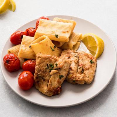 Barramundi fish fillets on a light grey plate with rigatoni and burst tomatoes.