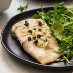 Baked fish on a black plate with fresh arugula.