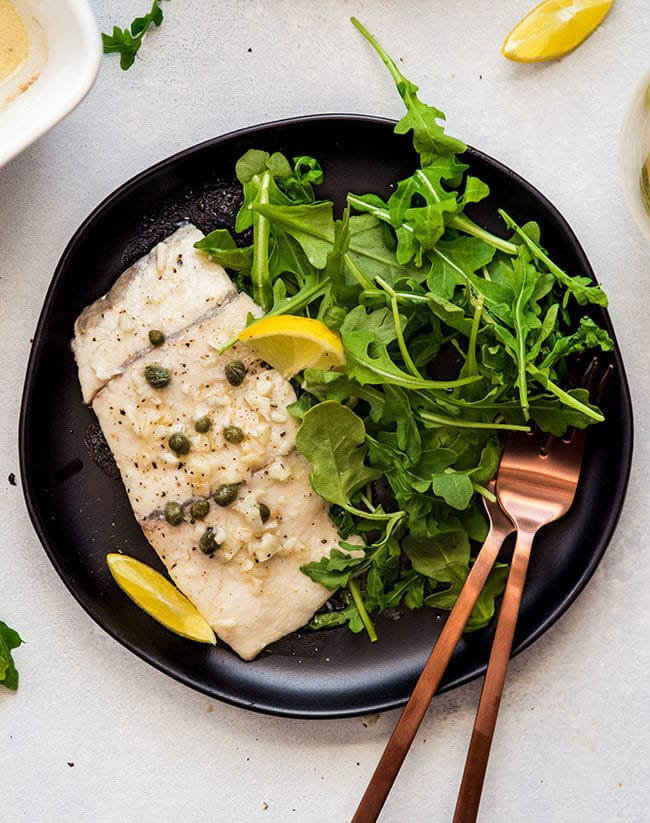 Overhead photo of baked white fish on a black plate with fresh arugula