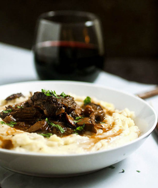 Braised beef short ribs and mashed potatoes in a shallow white bowl on a dark background