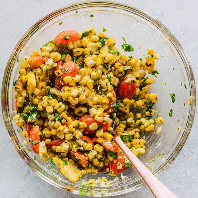 Corn and tomato salsa in a glass bowl.