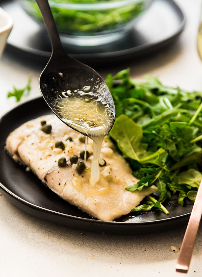 black spoon drizzling butter sauce over baked barramundi