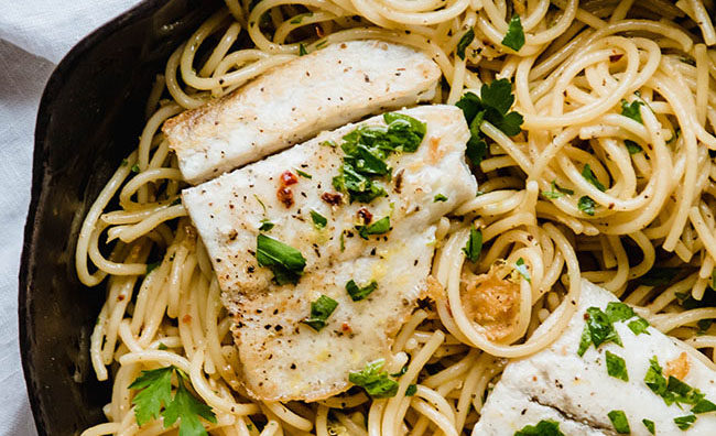 Barramundi fillet on top of spaghetti with fresh parsley