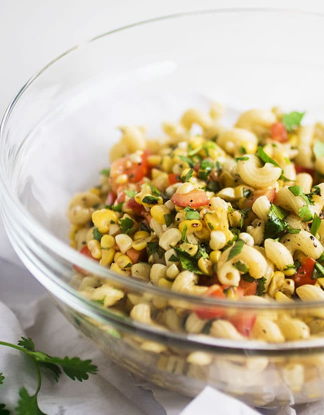 tomato pasta salad in a glass bowl with grilled corn and diced tomatoes