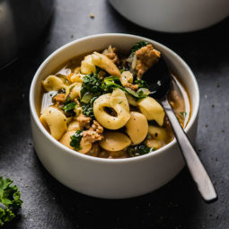 Tortellini soup with sausage and kale in a white bowl.