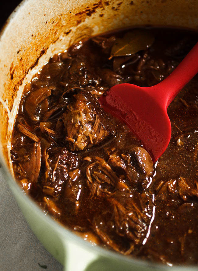 Red spatula stirring braised short ribs and red wine sauce in a large dutch oven.