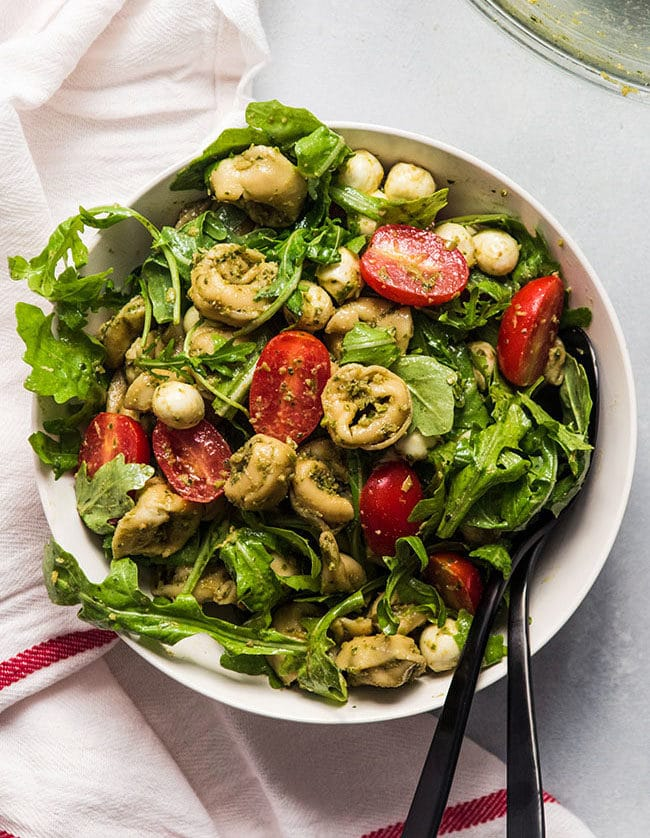 Overhead photo of tortellini salad in a white bowl with arugula and tomatoes