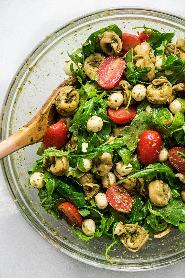 Tortellini salad with arugula and tomatoes in a glass bowl with a wooden spoon