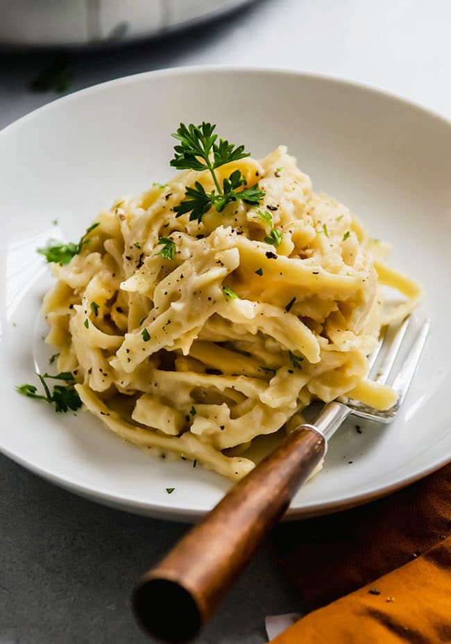 Fettuccine alfredo topped with fresh parsley on a white plate with a wooden fork.