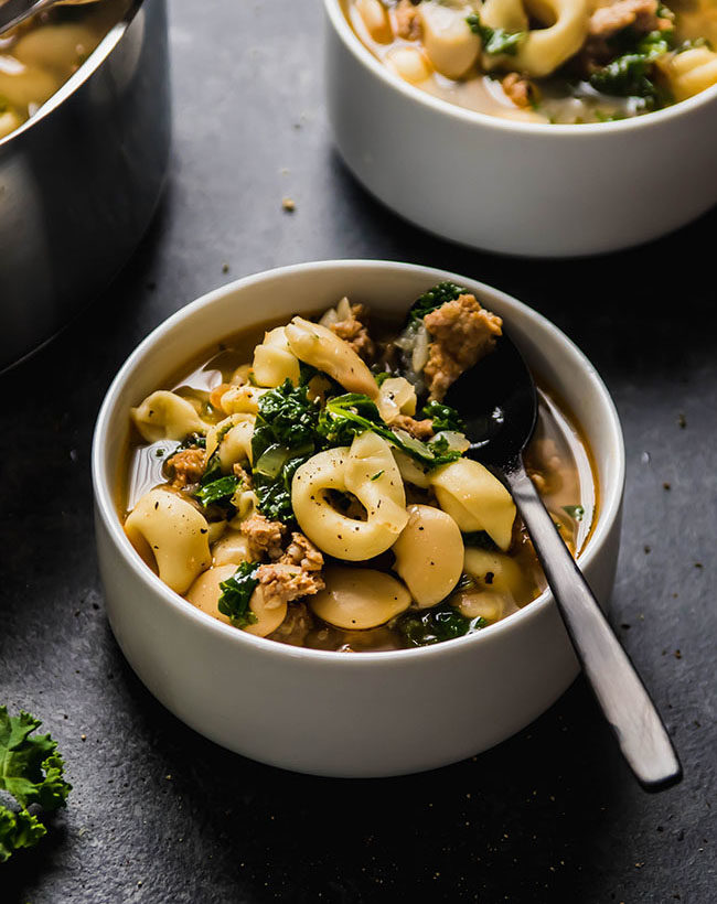 Tortellini soup with sausage and kale in a white bowl with a black spoon