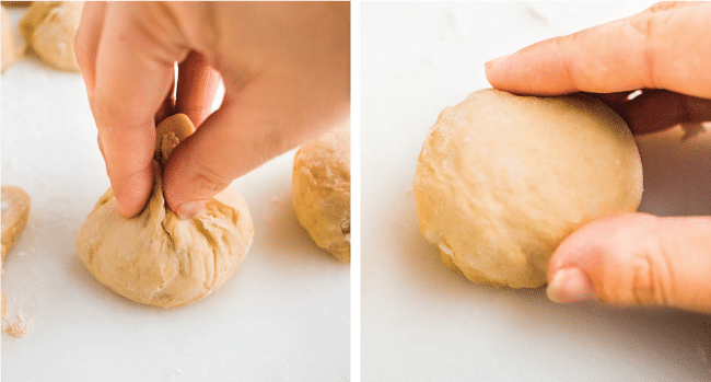 woman's hands forming a small roll of uncooked bread dough