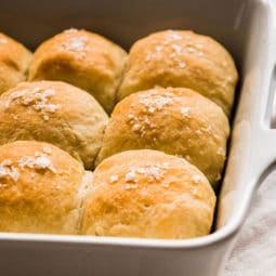 Fresh dinner rolls in a white casserole dish.