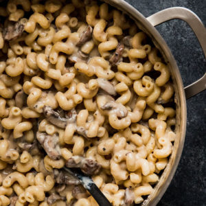 macaroni and cheese with mushrooms in a silver pot on a black background