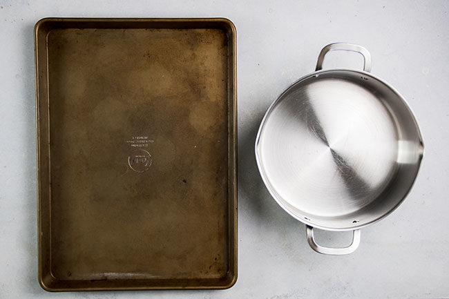 Baking sheet next to a stainless steel pot on a white table.