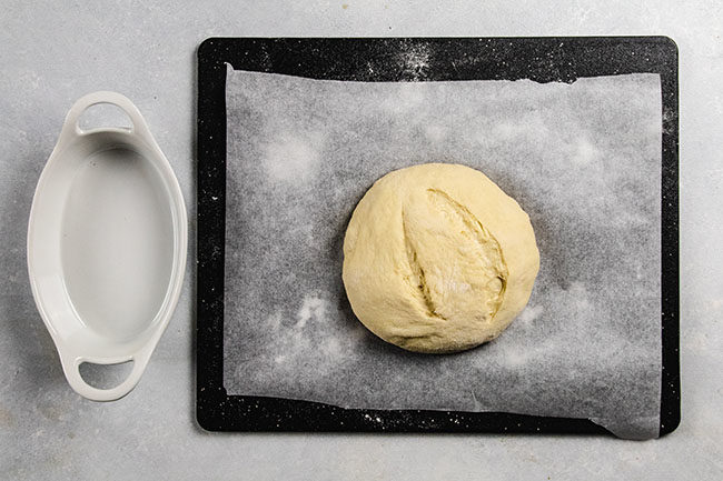 Bread dough on a black cutting board lined with parchment paper.