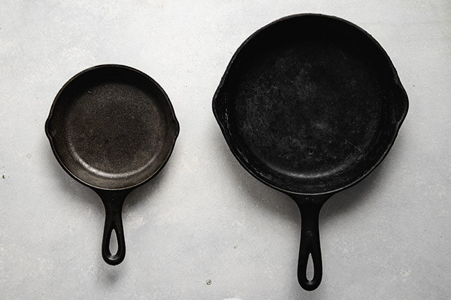 White table with a large cast iron skillet next to a small cast iron skillet.