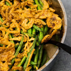 Black fork lifting green bean casserole out of a baking dish