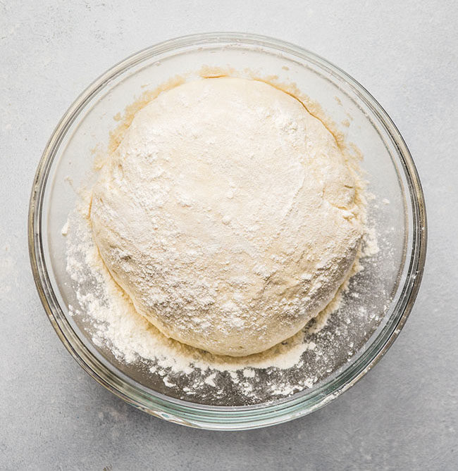 overhead photo of bread dough in a glass bowl on a white countertop