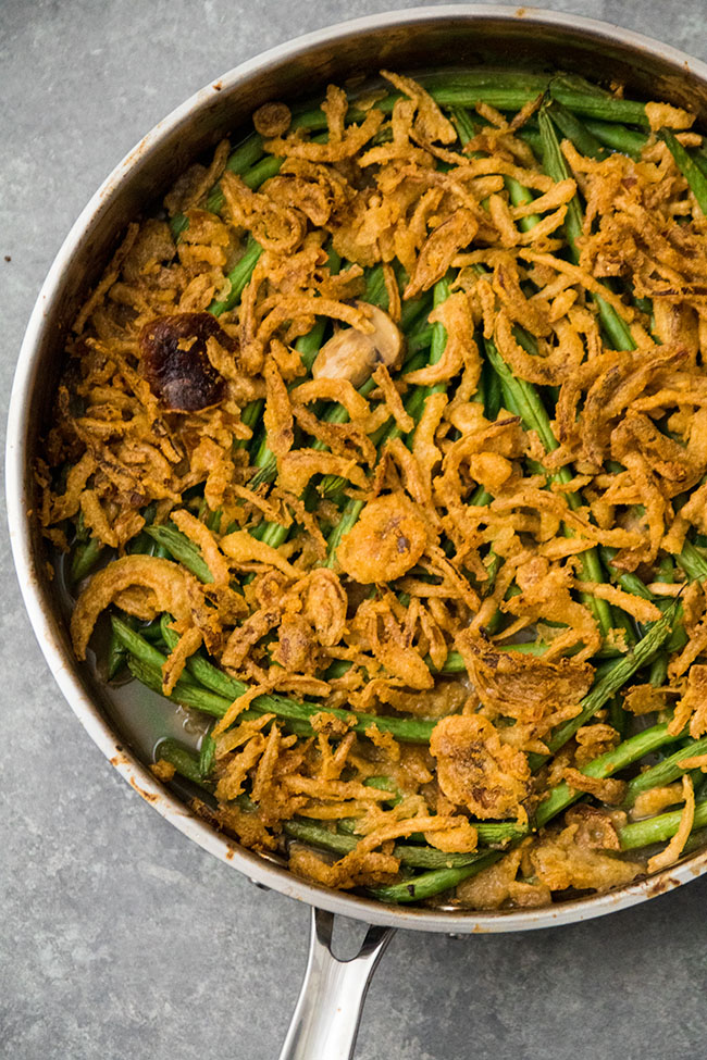 overhead photo of green bean casserole topped with fried onions in a large metal skillet
