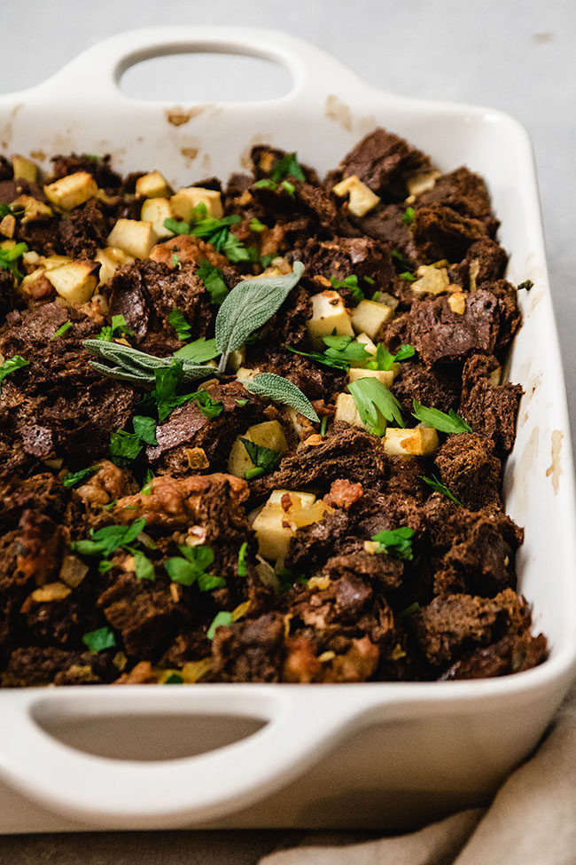 Pumpernickel stuffing in a white ceramic baking dish topped with fresh sage