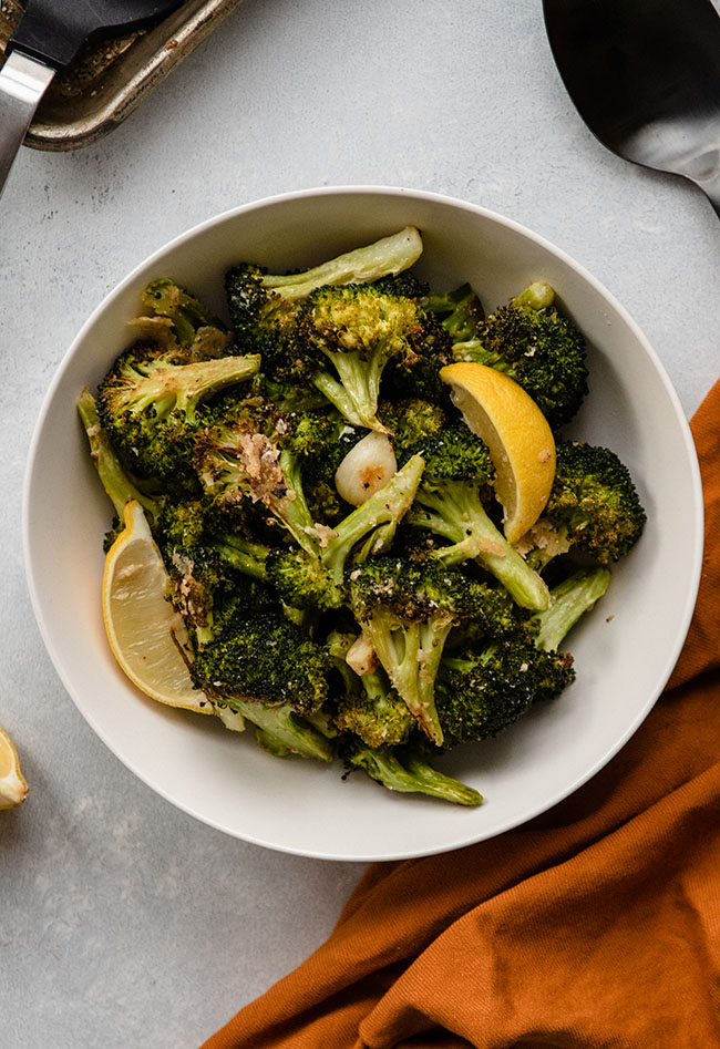 Overhead photo of roasted broccoli and lemon wedges in a white bowl next to a yellow napkin
