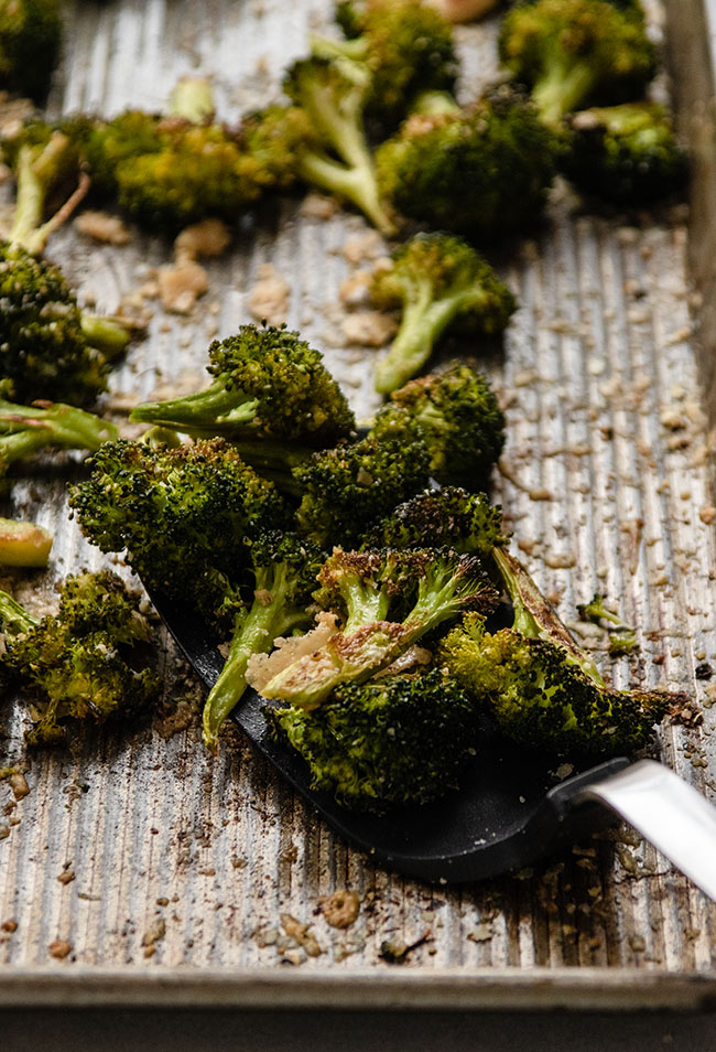 Black spatula lifting roasted broccoli off a sheet pan