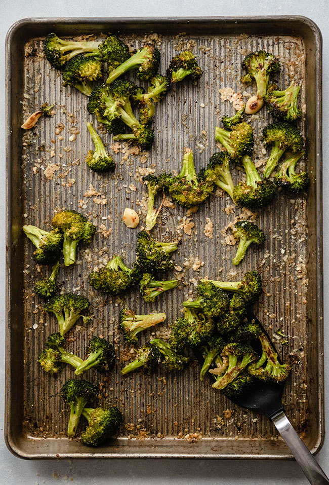 Overhead photo of roasted broccoli on a sheet pan with a black spatula