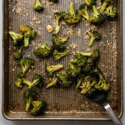 Black spatula lifting roasted broccoli from a sheet pan.