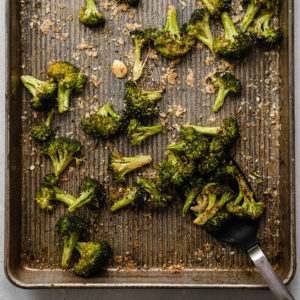 black spatula lifting roasted broccoli from a sheet pan