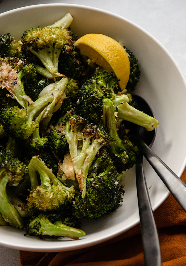 Roasted broccoli with a lemon wedge in a white bowl