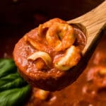 Wooden spoon lifting tortellini tomato soup out of a pot