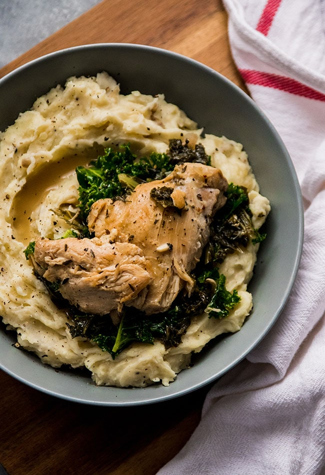 Chicken thighs in a shallow blue bowl with mashed potatoes and kale